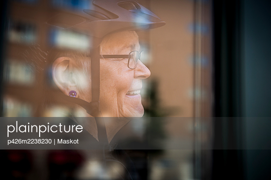 Smiling senior woman seen through window at home - p426m2238230 by Maskot