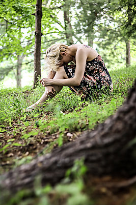 Sad woman with blond hair sitting in the forest - p1019m1425480 by Stephen Carroll