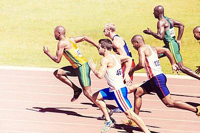 Sprinters racing on track - p1023m946878f by Tom Merton