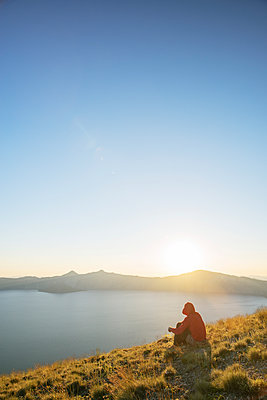 Hiker sitting on mountain at Crater Lake National Park against clear sky during sunset - p1166m1415114 by Cavan Images