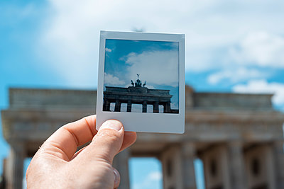 Man holding a polaroid of the Brandenburg Gate in Berlin, Germany - p1423m2210146 by JUAN MOYANO