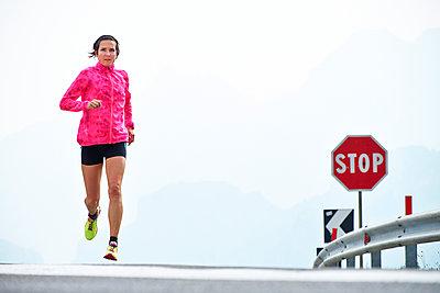 Italy, Trentino, woman running on road near Lake Garda - p300m1188849 by Michael Reusse (alt)