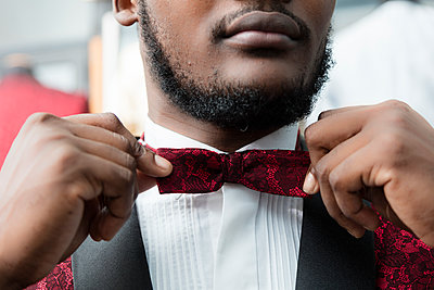 Close-up of a man wearing tuxedo in tailor shop adjusting the bow tie - p300m1568226 von Authentic Images