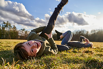 Portrait of happy boy with sister lying on a meadow - p300m2180051 by Stefanie Aumiller