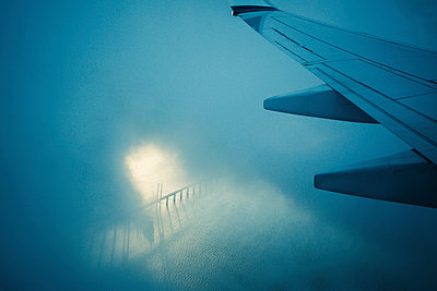 Airplane wing flying through clouds over water - p301m2070904 by Sven Hagolani