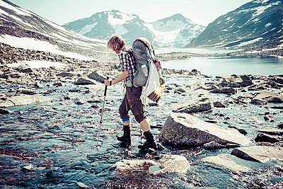 Side view of female hiker crossing river - p426m844649f by Katja Kircher