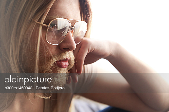 Portrait of pensive young man with long blond hair wearing spectacles - p300m1469942 by Retales Botijero
