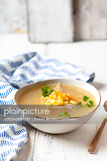 Bowl of homemade chicken stock with potatoes, carrots and parsley - p300m2081231 by Susan Brooks-Dammann