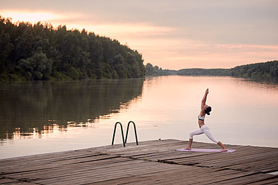 Woman practicing warrior 1 pose on pier by lake against cloudy sky during sunset - p1166m2011223 by Cavan Images