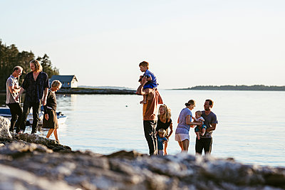 Family enjoying at beach against clear sky during sunset - p1166m2034327 by Cavan Images