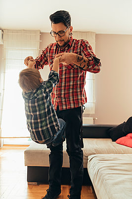 Father and son playing together at home - p300m1204482 by Zeljko Dangubic