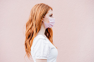 portrait of beautiful redhair woman over pink wall weraring face mask, Madrid, Spain - p300m2274013 von Eva Blanco