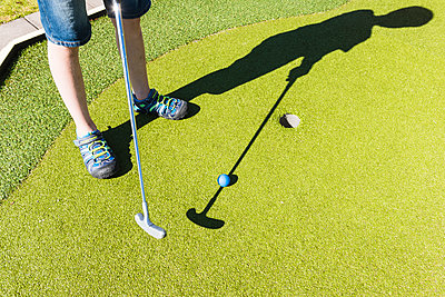 Boy playing mini golf - p312m1107514f by Mikael Svensson