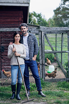 Portrait of couple standing at poultry farm - p426m1003623f by Maskot