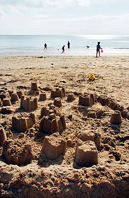 Sandcastles on beach with silhouettes of family group - p5970135 by Tim Robinson