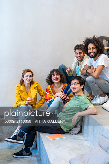 Portrait of group of friends sitting on stairs having a drink - p300m2113858 von VITTA GALLERY