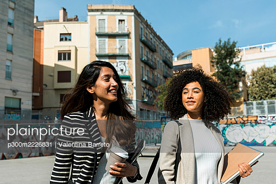 Female coworkers looking away while standing on street in city during sunny day - p300m2226831 by Valentina Barreto