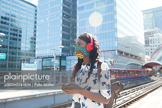 Businesswoman wearing face mask and headphones looking away while standing at station - p300m2241636 by Pete Muller