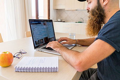 Bearded young man working on laptop at home - p300m1580772 von VITTA GALLERY