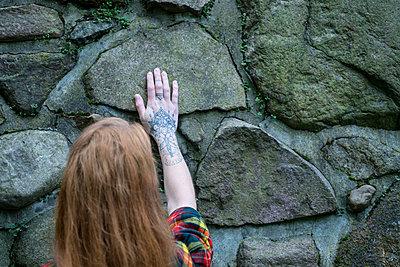 Rothaarige Frau an einer Mauer - p427m1537847 von R. Mohr