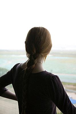 Junge Frau mit geflochtenem Zopf betrachtet die Aussicht - p4903385 von Tobias Thomassetti