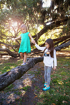 Girl holding hands with sister walking on tree branch - p924m1513615 by Kinzie Riehm