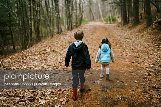 Two kids walking on a path in the woods together during a hike - p1166m2268869 by Cavan Images