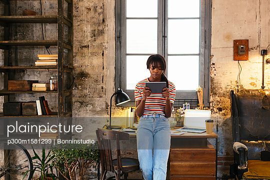 Young woman standing in front of desk in a loft using tablet - p300m1581299 von Bonninstudio