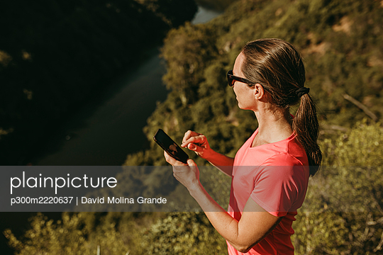 Woman using mobile phone while standing on mountain at Sierra De Hornachuelos, Cordoba, Spain - p300m2220637 by David Molina Grande