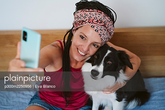 Smiling woman taking selfie with pet through mobile phone while sitting on bed at home - p300m2250956 by Eva Blanco