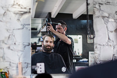Barber blow-drying hair of a customer - p300m1166035 by zerocreatives