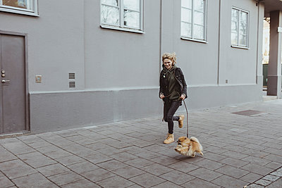 Full length of happy woman running with her Pomeranian dog on footpath by building in city - p426m2194904 by Maskot