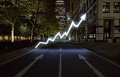 Glowing arrow symbol in city street at night, London, UK - p429m976364 by J J D