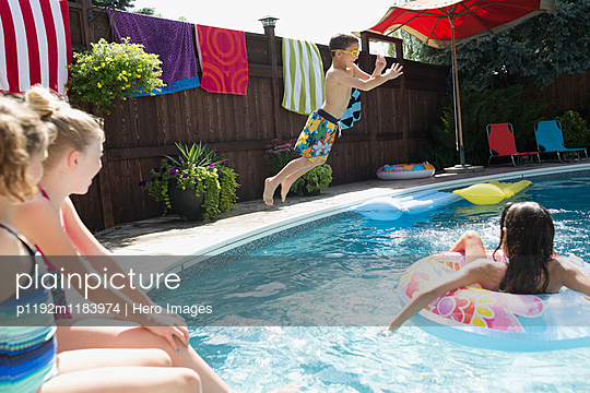 Boy jumping into sunny swimming pool - p1192m1183974 by Hero Images