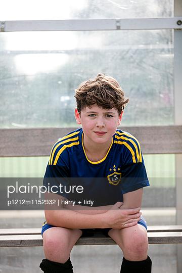 Junge auf der Bank auf dem Sportplatz - p1212m1152932 von harry + lidy