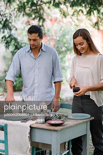 Couple preparing a romantic candelight meal outdoors - p300m2068801 von Alberto Bogo