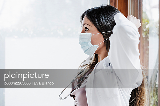 Female medical professional wearing protective face mask during COVID-19 - p300m2265066 by Eva Blanco