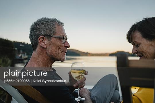 Reifes Paar trinkt Weißwein am Baldeneysee - p586m2109053 von Kniel Synnatzschke