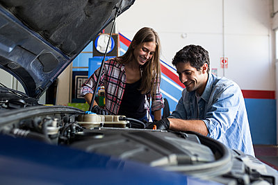 Cheerful man and young woman working together on car repair service and fixing car engine - p300m2155101 by Andrés Benitez