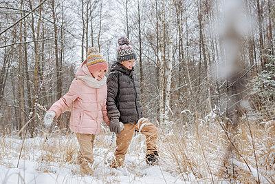 Two siblings walking hand in hand in winter forest - p300m2166847 by Ekaterina Yakunina