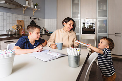 Boy giving book to mother while brother doing homework at table in kitchen - p300m2277686 by Katharina und Ekaterina