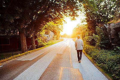 Man walking on a road at sunset in Bohuslan, Sweden - p352m1523662 by Benjamin Rudström