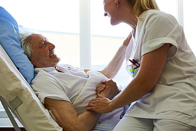 Side view of happy senior man talking to female nurse on hospital bed - p426m1494044 by Maskot