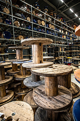 Empty cable drums stacked in warehouse - p429m803062f by Arno Masse