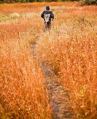 Caucasian man walking on path carrying fishing rod - p555m1301787 by Mike Kemp