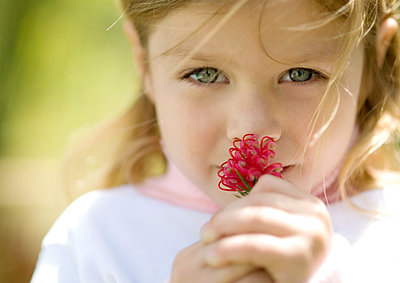 Girl smelling flower - p6237148f by Eric Audras