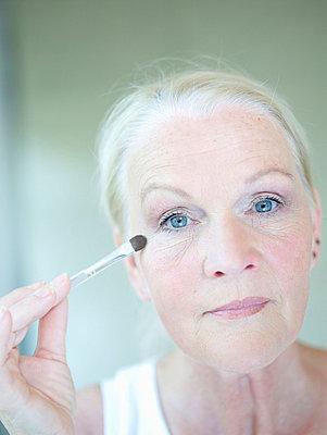 Aeltere Frau traegt Lidschatten auf  - p6430361f von senior images RF
