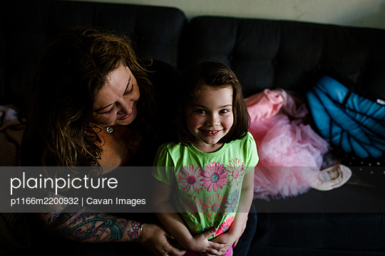 Niece and Aunt Sitting on Couch, Smiling - p1166m2200932 by Cavan Images