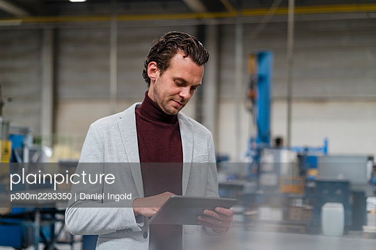 Mid adult businessman using digital tablet at industry - p300m2293350 by Daniel Ingold