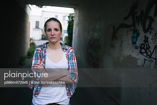 Junge Frau steht mit verschränkten Armen in einem Durchgang - p586m972945 von Kniel Synnatzschke